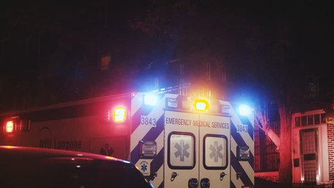View of rear doors and flashing lights of emergency service ambulance moving away from accident scene at nighttime.