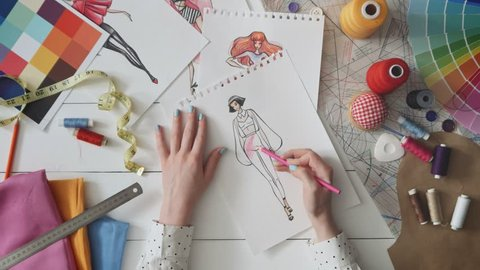 Fashion designer drawing clothes sketch