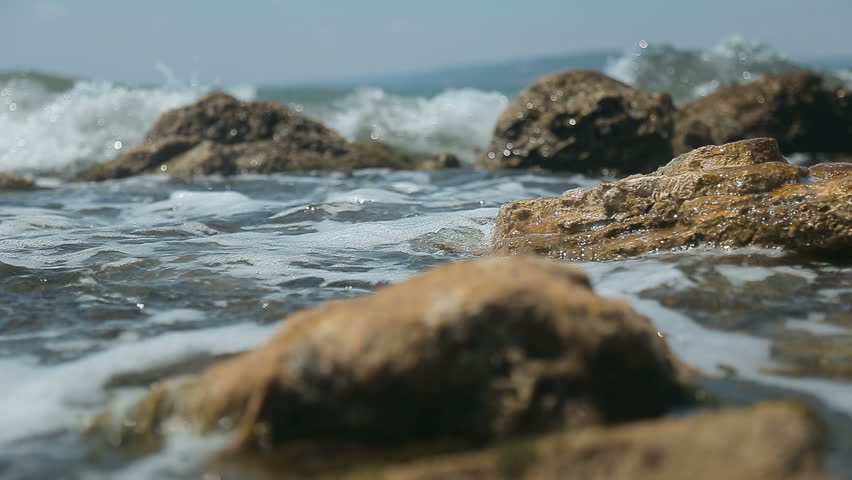 Strong waves washing rocks at the seaside on hot summer noon