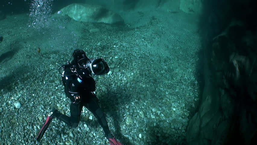 Camera operator diver underwater in transparent river Verzasca. Shooting a frame of picturesque nature on background of huge smooth stones. | Shutterstock HD Video #1015244077