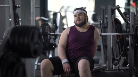 Tired fat man having rest after workout exercise, strength of muscles, training