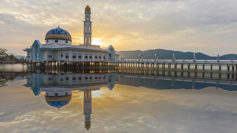 Time lapse of sunrise and scattered clouds at Masjid 1000 Selawat Mosque with reflections in Pangkor Island, Perak, Malaysia at dawn from night to day. Motion timelapse Slide up. Prores Full HD 1080p.