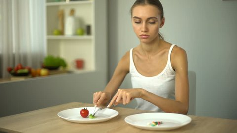 Girl eats spinach, looks at anti-obesity pills, drugs as easy way to lose weight