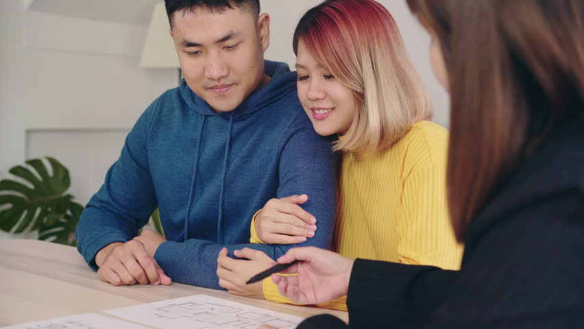 Happy young Asian couple and realtor agent. Cheerful young man signing some documents while sitting at desk together with his wife. Buying new house real estate.