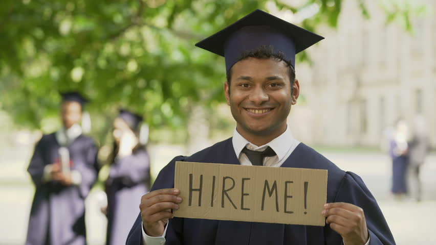 Young man in graduation gown holding table hire me, smiling, youth employment