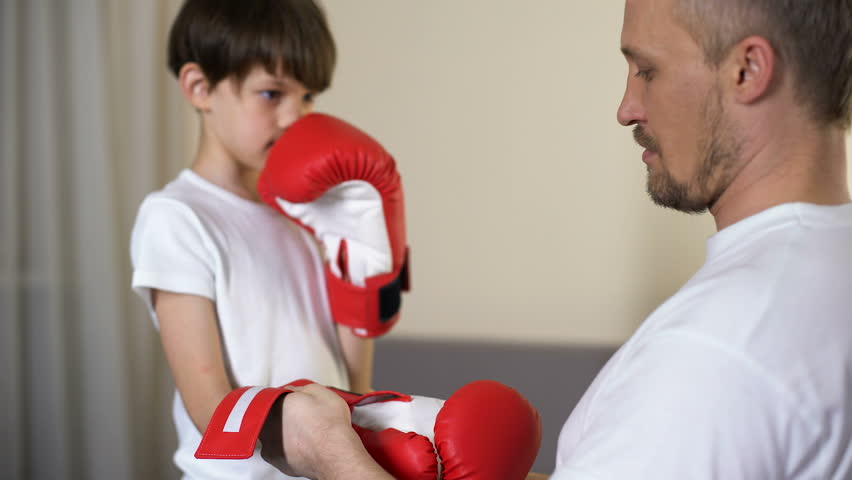 Caring father putting on son arms boxing gloves and teaching to defend himself