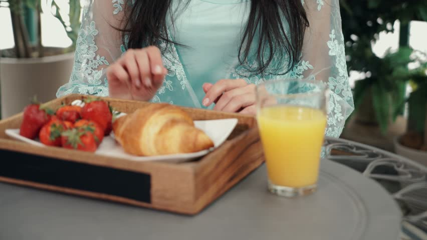 Young dark hair woman in a dress taking a croissant from a plate with strawberries in summer cafe. Front view Tilt up real time medium shot #1015381927