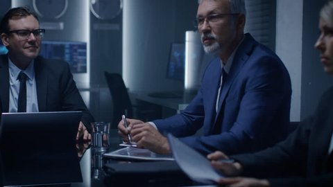 Chairman of the Board of Directors Making a Speech to His Professional Colleagues thus Saving Corporation in Emergency Situation. In the Background Monitors with Various Data. Shot on RED EPIC-W 8K.