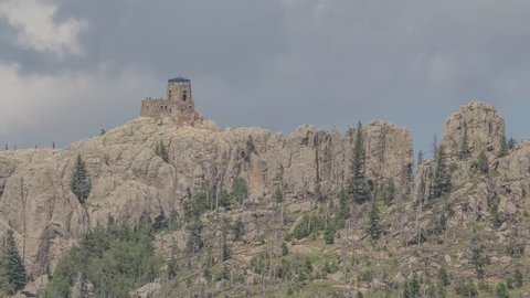 A Telephoto Close Up Shot on the Stone Fire Watchtower atop Black Elk Peak in South Dakota's Black Hills with Patterns of Clouds in the Background 4K Timelapse