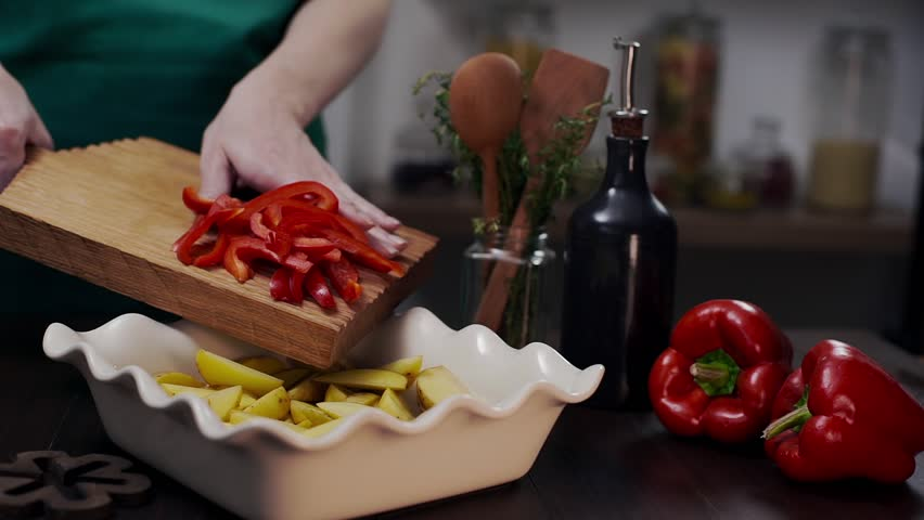 The cook makes meal with red bell pepper and other vegetables, chef adds bell pepper to the meal, vegetarian and healthy recipes, food with pepper