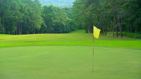 Golf sport concept, Beautiful golf course on hills in open tournament, fairway and layout beauty in forest. Yellow flag on green and beautiful nature of forest. It green meadow and lawn for player.