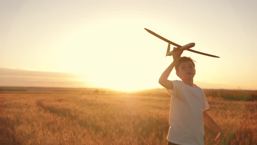 Happy child runs with a toy airplane on a sunset background over a field. The concept of a happy family. Childhood dreams | Shutterstock HD Video #1015426687