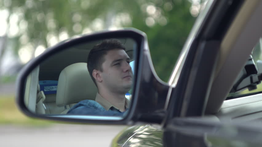 Young man driving a car checking behind him looking anxiously in the side view mirror through the open window in a close up focus of his face in the reflection. | Shutterstock HD Video #1015444897