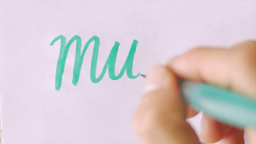 Hand writing the word MUM in an artistic way with a green brush pen on white paper