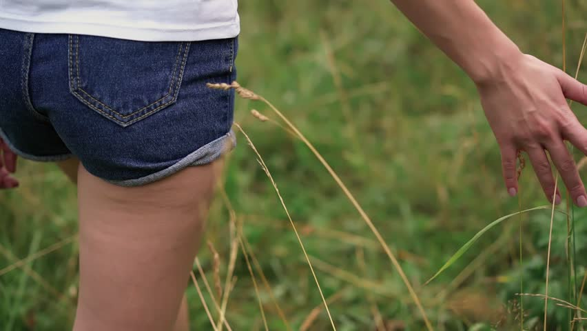 Rear view of an unrecognizable young girl wearing jeans shorts walking in a field or park on a summer day and touching the grass. Tracking slow motion medium shot