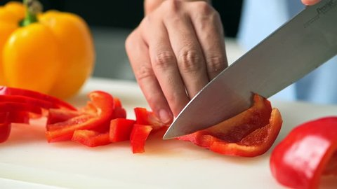 Woman slicing red bell pepper in kitchen close up. Young asian housewife slicing raw red bell pepper to prepare for food and dinner. Home cooking concept.
