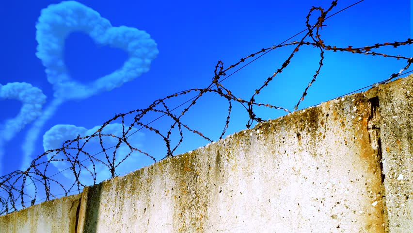 Heart-shaped cloud in the sky behind barbed wire