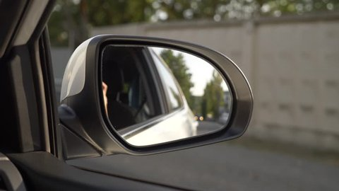 View out the rearview mirror, when the car passes along the road in the summer. 4k, slow-motion shooting