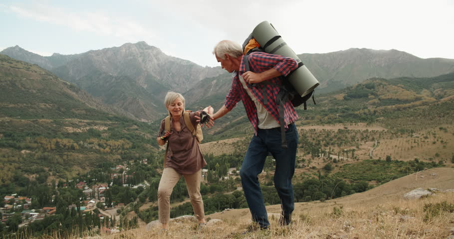 Mature caucasian senior on a hiking adventure taking wife's hand helping her climb up a mountain. tourism concept 4k | Shutterstock HD Video #1015494787