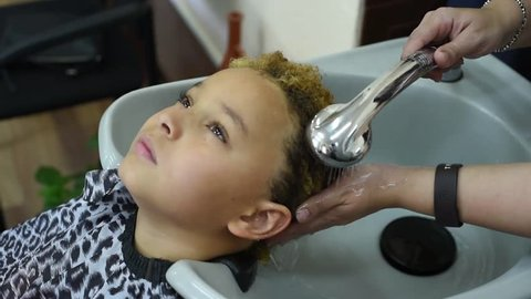 The process of washing hair in the Barber shop. The boy washed his head in the Barber shop. ?ute african american  boy  washing hair after coloring his hair.  Children in hair salon.