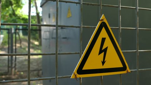 Sign High Voltage Warning With Lightning Arrow Placed On A Metal Fence