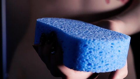 Woman holding in hand new shower sponge. Bath room routine, advertising of body washing stuff. Sponge close up isolated, camera moving in slowmotion and showing the dry buff. Preparing for bathing