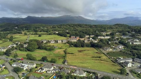 Aerial view, rise up move. Drone panorama of Penrhyndeudraeth town in Snowdonia mountains in Wales