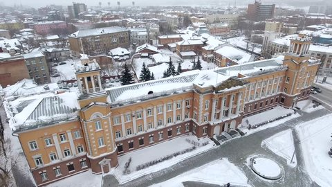 Helicopter drone flight above central square of Irkutsk city. Siberian cold winter with snow. Tourism in Russia. White rooftop old Stalin heritage column Administration building. Cinematic footage