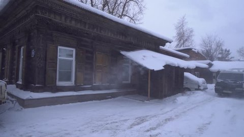 Cold Siberian winter wooden old house Steadicam cinematic. Unique authentic Russian style wood carving architecture. Irkutsk center tourist attraction. White snow wind blizzard. Gimbal professional 4k