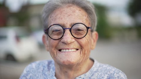Portrait of happy elderly woman with black round glasses looking at camera and smiling with white teeth.