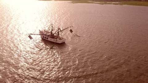Aerial circling shot of commercial shrimp boat at first light in south  carolina