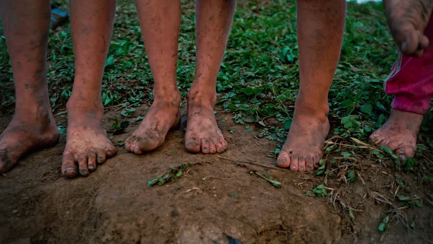 Close-up barefooted dirty feet of a children standing on a damp ground