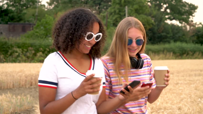 Slow motion tracking video clip of pretty blonde girl and mixed race teenager young women wearing sunglasses drinking coffee and using mobile cell smart phones