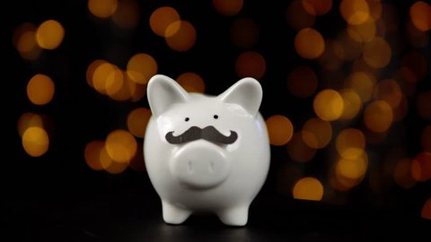 Piggy bank wearing a fake mustache and rotating counterclockwise against a black background with yellow lights, someone puts a coin in a money box, celebrating a movember.
