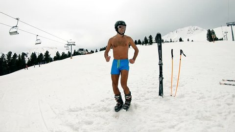 Winter party concept. Smiling funny man dancing naked wearing boots, helmet and goggles on ski slope, slow motion