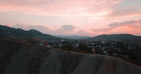 Mountains Peaks, Sunset Sea and the city. Epic on the edge of the mountain valley with rocks and sun flare. 4k drone flight. Aerial establisher. Europe green nature. Film vintage colors.