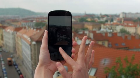 young woman is taking photos of Prague panorama, close-up view of hands