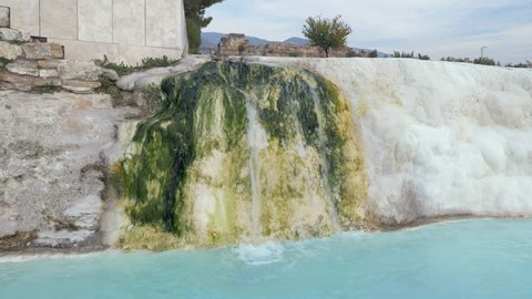 Travertine creek with water flowing and falling in hot water springs in Pamukkale, Turkey