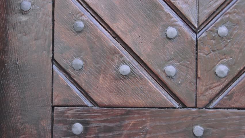 Rustic brown wooden door texture. Fragment of wooden door with metal rivets. Texture of old wood door
