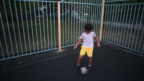 Cool football player boy try to be goalkeeper and playing on sport playground. Sportive and active children. Mixed kids playing football downstairs. Curly african American boy playing and training