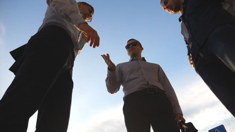Three businessmen farewell with each other each other and farewell and diverge in different directions. Colleagues shake hands with blue sky at city background. Business handshake outdoor. Slow motion
