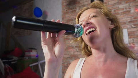 Close up. a woman screaming to a microphone. a woman sings karaoke into a microphone in a home setting. 4k, slow motion