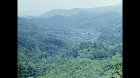 1950s: Mountains covered with trees. Man sits on box in front of mountain range. Woman walks in front of mountains.