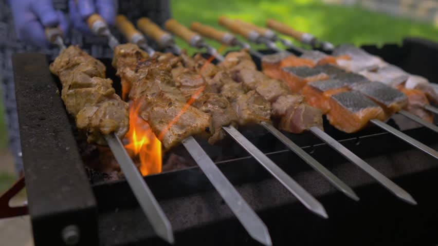 Cooking kebab on barbeque. Fresh meat and fish are cooked on fire | Shutterstock HD Video #1015673167