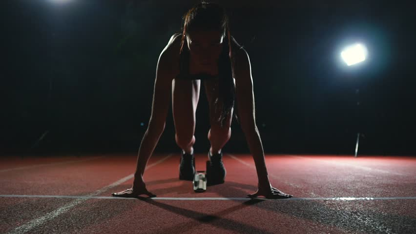 Professional woman athlete on a dark background gotovtes to run the sprint of Jogging shoes in sneakers on the track of the stadium on a dark background. Close up