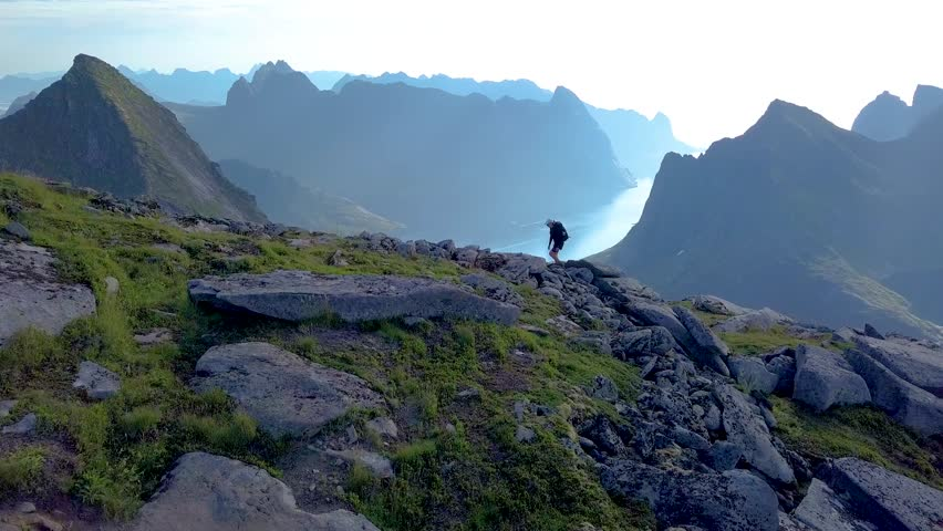 Aerial view of girl with a backpack rises on a mountain ridge. Beautiful view of the peaked tops of the Lofoten Islands. Norway 4k