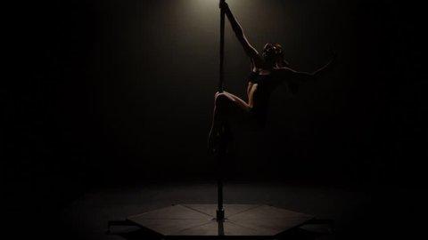 Female dancer sexy poledance . Black background. Slow motion. Silhouette