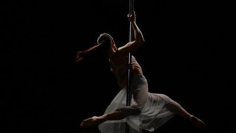 Female dancer performs sexy poledance on pole . Black background. Slow motion
