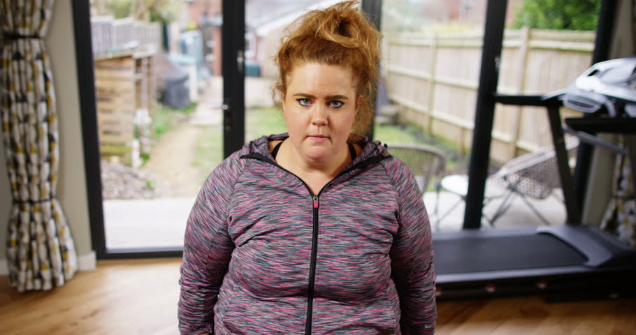 4K Funny fat & unfit girl straining to lift small weights while staring at camera