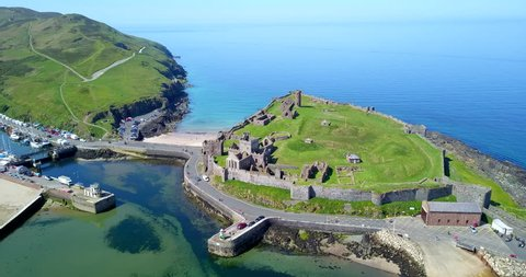 Drone flying over Peel Castle on Isle of Man, landmark building in Peel on the Isle of Man, originally built by Vikings. Aerial view of beautiful sea village with old monument seen from the sky